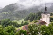 GRUYERES, SWITZERLAND - JULY 8, 2014: St. Theodul's Church, Gruyeres. Seen from Gruyeres Castle it w