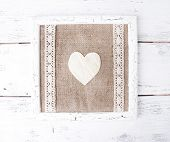 Wooden frame with paper heart isolated on white