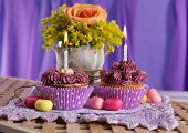 Tasty cupcakes on table, on fabric background
