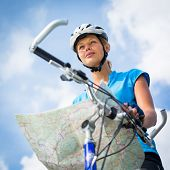 Female cyclist, reading a map, finding her way