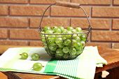 Fresh gooseberries in basket on wall background