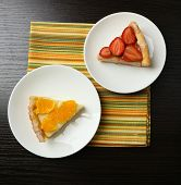 Piece of homemade orange and strawberry tarts on plate, on color wooden background
