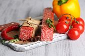 Tasty salami sausage, vegetables and spices on paper on wooden background