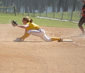 picture of softball  - Close up of girl covering first base in softball game - JPG