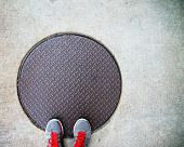 stock photo of manhole  - a pair of feet on a manhole cover - JPG