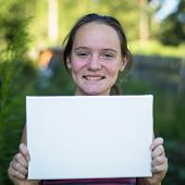 Banner for your message: Fun teen-girl holding clean white sheet paper, outdoors.