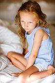 Sweet little girl with curly hair in light blue pajama sitting on bed