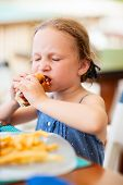 Adorable little girl enjoying eating hot dog for lunch at restaurant