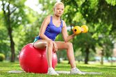 Young woman exercising with a dumbbell and pilates ball in park