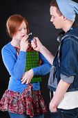 stock photo of polite girl  - Naughty boy persuaded polite girl to smoke joint first time - JPG