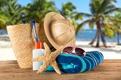 Close-up of summer accessories on sandy beach.