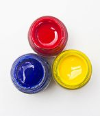 Top View Of Opened Bottles Of Primary Color On White Background.