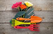Gardening tools, gloves and gerbera flowers on wooden table background