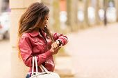 young african woman looking at her watch in urban street