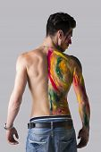 Young Man Seen From The Back With Skin Painted With Colors