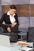Young businesswoman unpacking briefcase upon arrival at office.