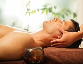 foto of massage oil  - Handsome man having face massage in spa salon - JPG