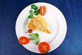 food : vegetable casserole piece over white plate served with parsley and tomatoes on blue table