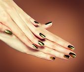 A slender hand with metallic gold nails