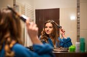 Pretty, young woman curling her hair in front of her bathroom mirror