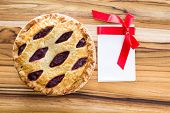 stock photo of cherry pie  - view form above of a fresh baked cherry pie with a blank note with a red ribbon - JPG