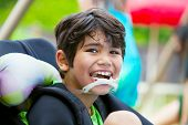 stock photo of biracial  - Handsome disabled eight year old biracial boy smiling and relaxing in wheelchair - JPG