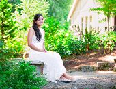 Beautiful Biracial Bride In White Lace Wedding Dress Sitting On Bench Outdoors, Smiling