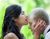 Biracial bride kissing Caucasian groom on forehead