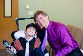 stock photo of biracial  - Caucasian father in purple dresshirt and necktie sitting next to biracial disabled son in wheelchair - JPG