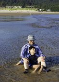 Caucasian Father Playing In Water On Beach With Disabled Son