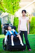 Disabled Little Boy In Wheelchair With Sister On Grassy Lawn Outdoors