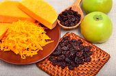 Ripe Raw Pumpkin With Grated Pumpkin, Apples And Heap Of Raisins On The Ceramic Brown Plate