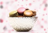 Colored macarons inside bowl on colored background