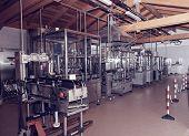 Wine bottling equipment line in a hangar, toned image