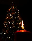 Bright Candle In front of Christmas tree