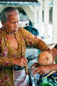 Old Woman Opening Coconut