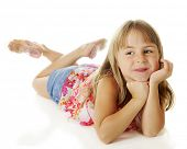 A pretty, young elementary girl happily relaxed on the floor with her head supported by her hands.  On a white background.