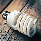 Close Up Of Energy Saving Light Bulb On Wooden Desk. Vintage Stylized.