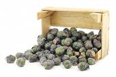 purple brussel sprouts in a wooden crate on a white background