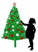 toddler girl putting decoration on Christmas tree