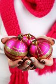 Christmas decorations in female hands on color background