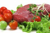 fresh raw beef meat steak on green salad with cherry tomatoes