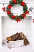 Fireplace with firewood and Christmas wreath on white wall background