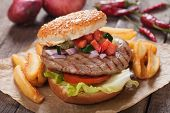 Hamburger with french fries, garnished with tomato, cucumber and onion