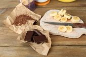 Sliced banana on cutting board and chopped chocolate, on wooden background