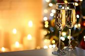 Two glass with champagne with chocolates and baubles on table on Christmas tree and fireplace background