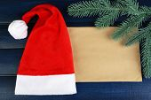 Santa red hat with branch of fir-tree and sheet of paper on color wooden background