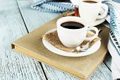 Cups of coffee on book on color wooden background
