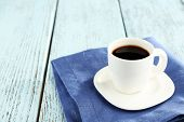 Cup of coffee on blue napkin on color wooden background