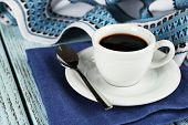 Cup of coffee on blue napkin with spoon and tablecloth on color wooden background